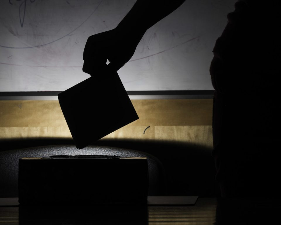 silhouette of a person placing a polling card into a ballot box